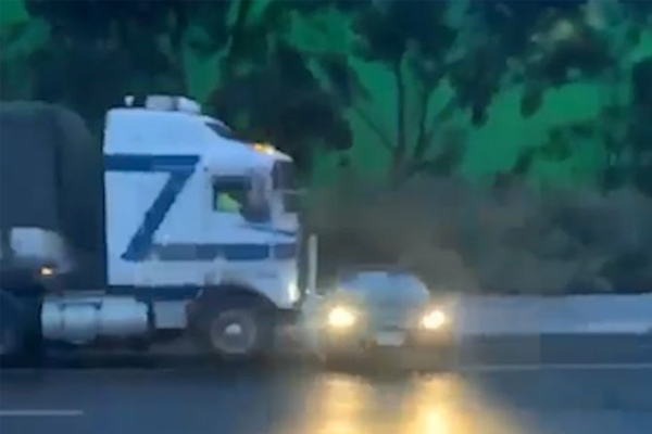 Article image for WATCH   Truck pushes car along wet freeway